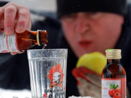 мужчина наливает боярышник в стакан