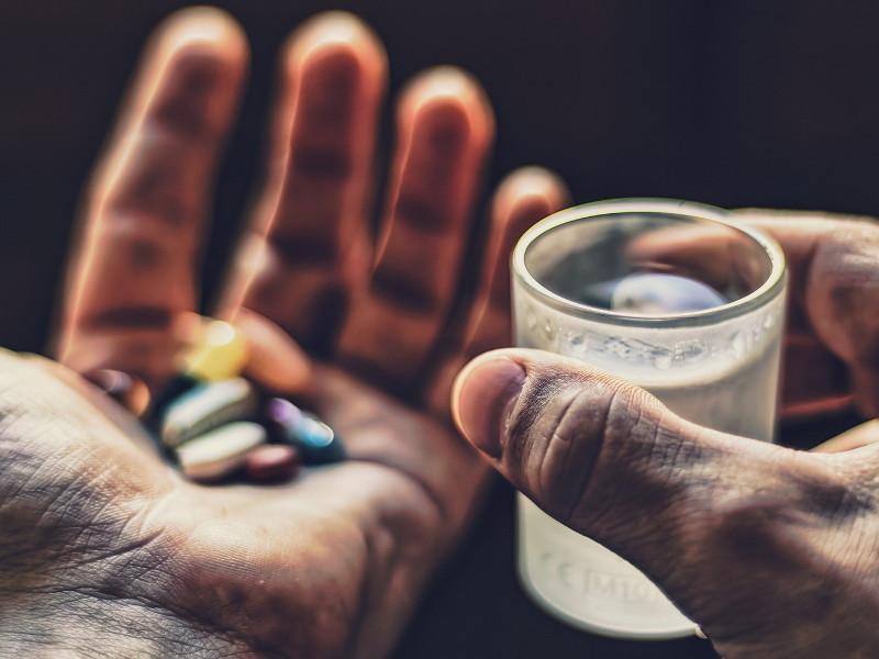 ладонь с таблетками трамадола и стакан с водой